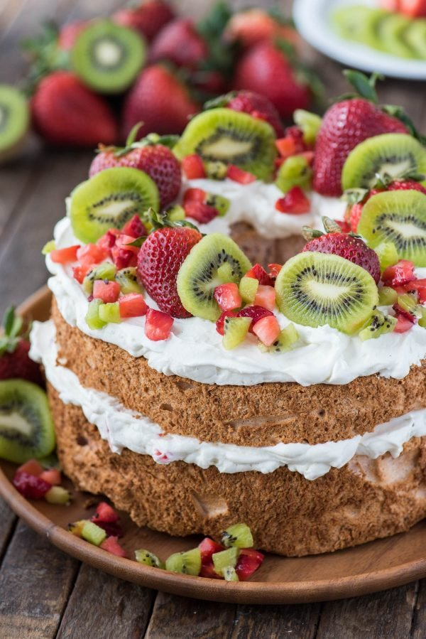 strawberry angel food cake topped with whipped cream, whole strawberries, chopped strawberries and kiwi on wooden serving tray