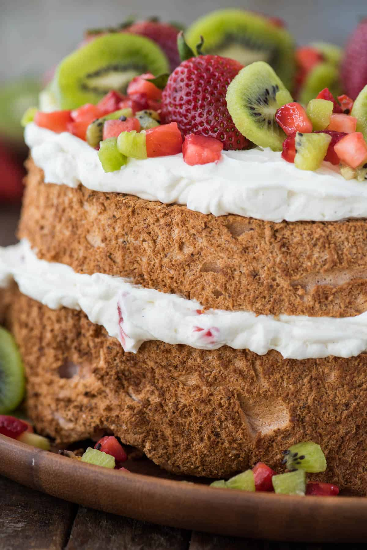 close up image of the side of strawberry angel food cake with whipping cream, strawberries and kiwi