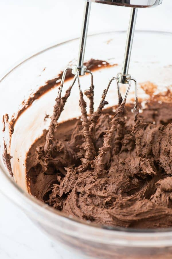 chocolate frosting in glass mixing bowl with electric mixer