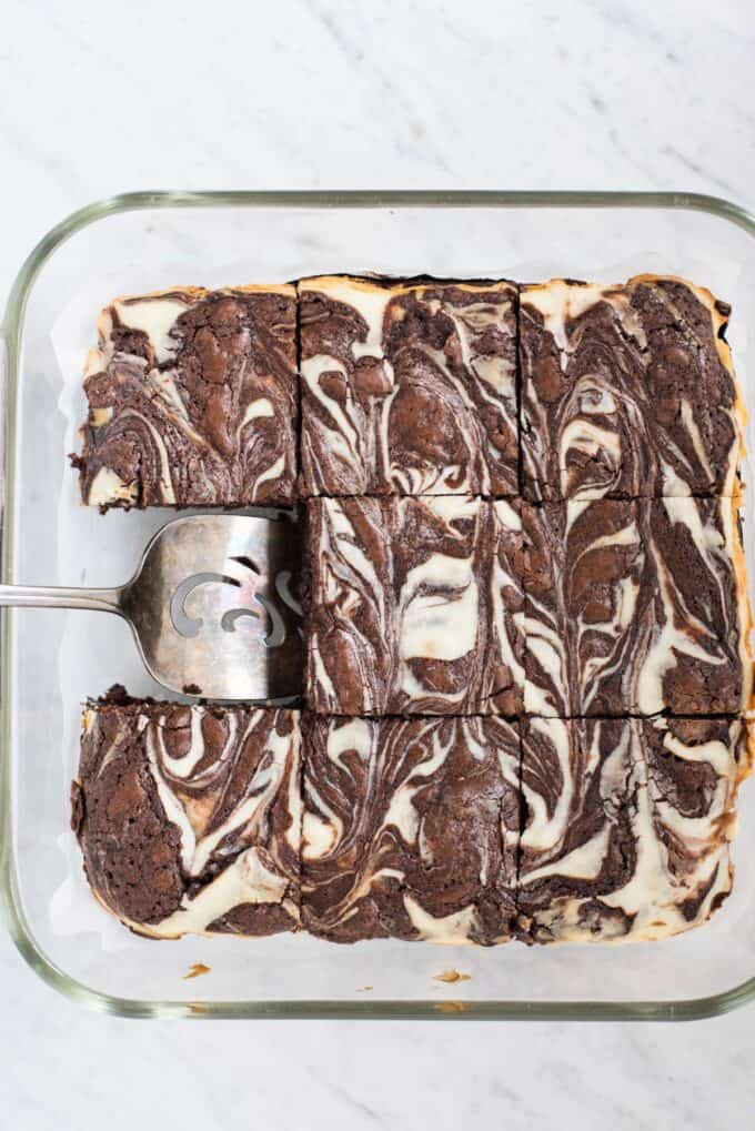 cream cheese swirl brownies cut into squares in glass pan