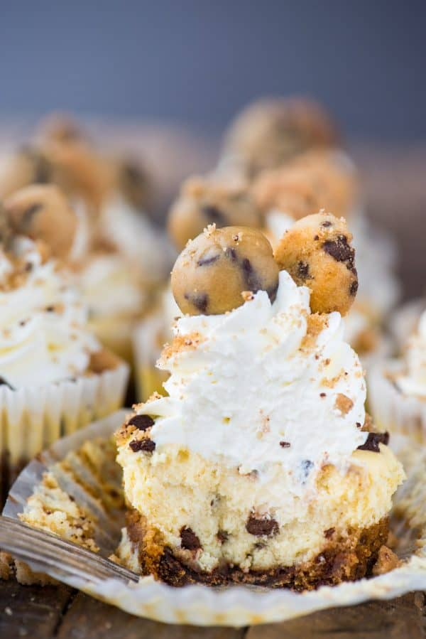 mini chocolate chip cookie dough cheesecake with bite removed on wood background