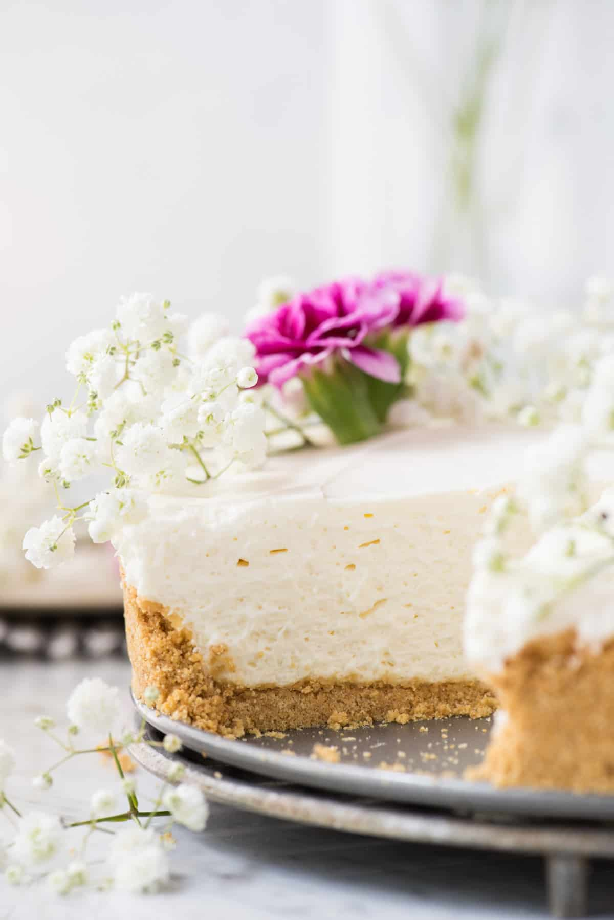 side shot of no bake cheesecake with white and pink flowers on white marble background