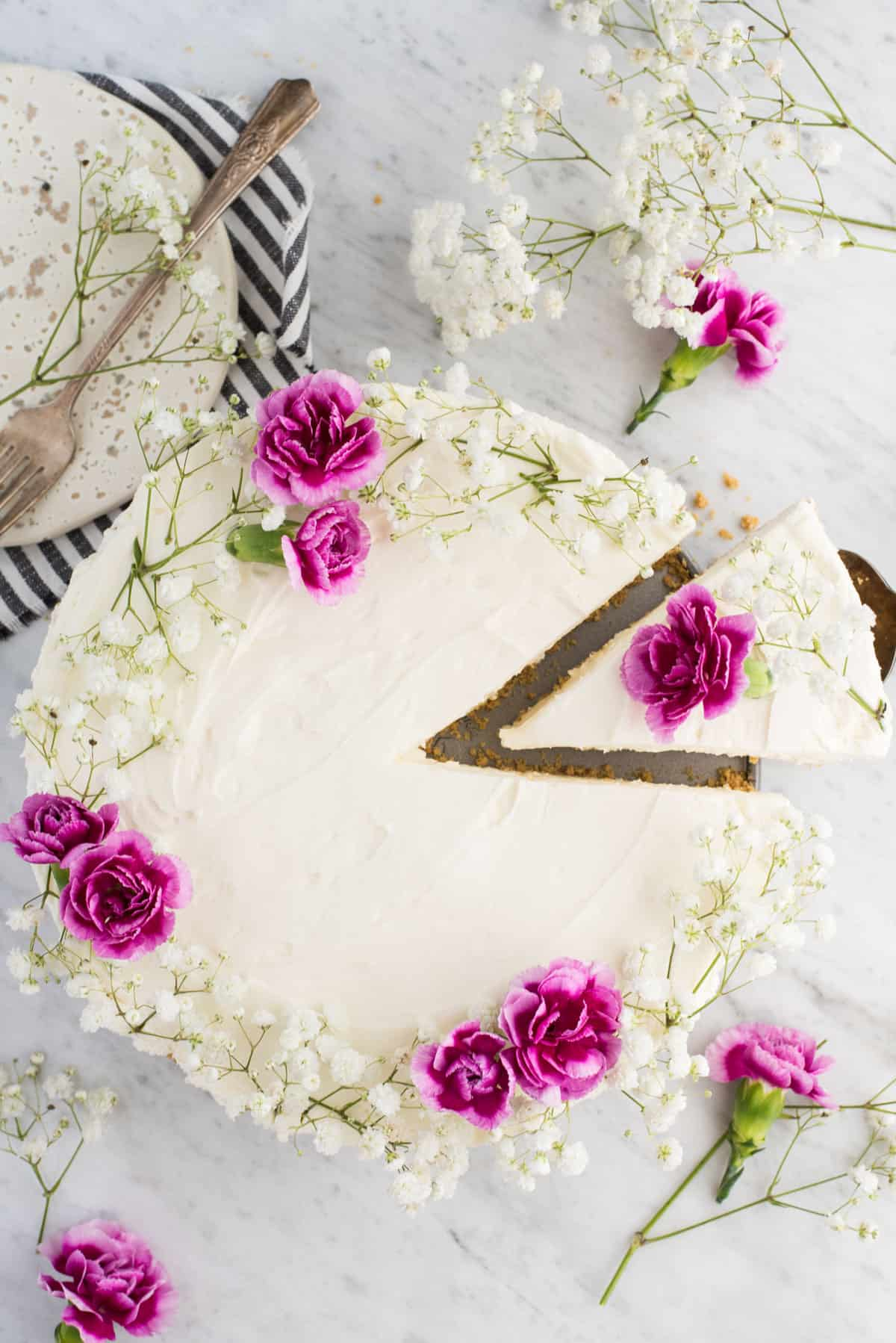 aerial view of whole no bake cheesecake with white and pink flowers on white marble background with one slice slightly removed