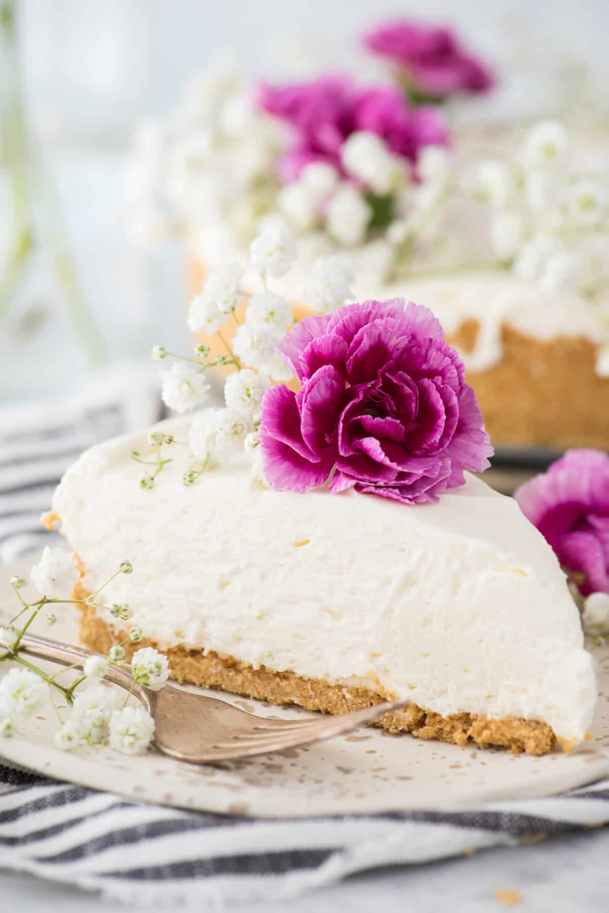 slice of no bake cheesecake with white and pink flowers on white plate
