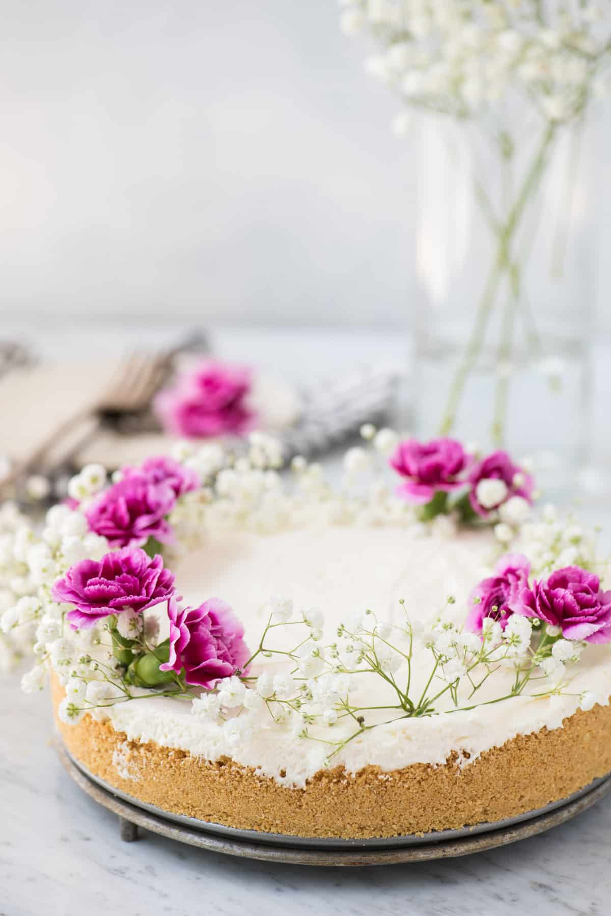 whole no bake cheesecake with white and pink flowers on white marble background