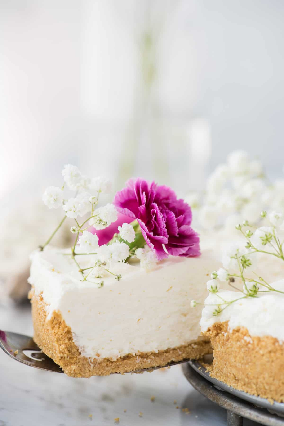 slice of no bake cheesecake with white and pink flowers being removed from rest of cheesecake