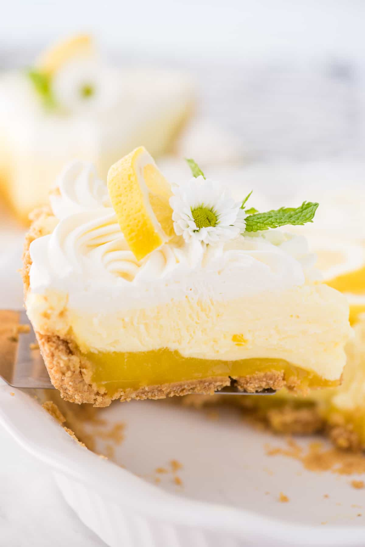 a slice of no bake triple layer lemon pudding pie being removed from white pie plate
