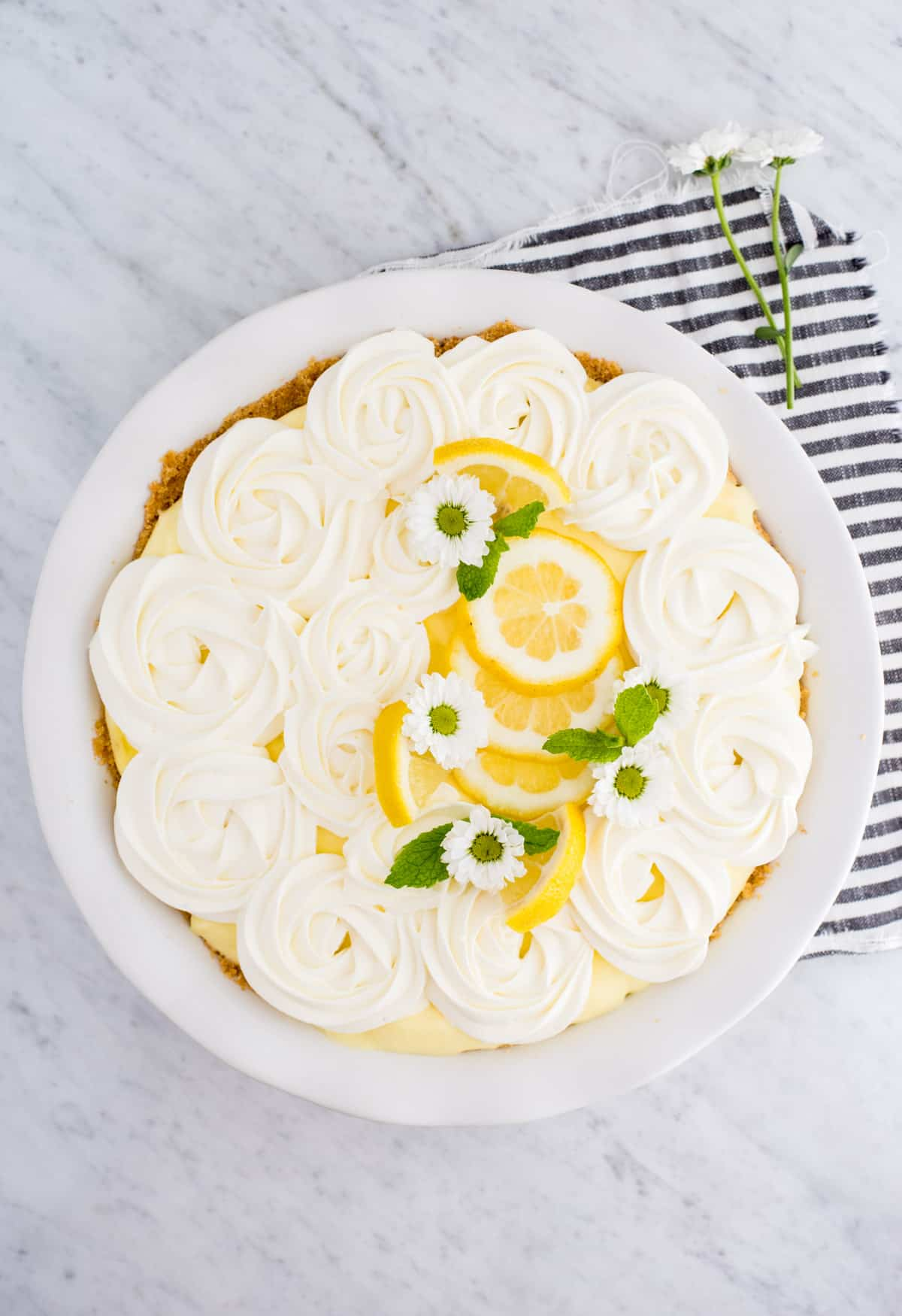 no bake triple layer lemon pudding pie in white pie plate with whipped cream, lemon slices, white flowers and mint leaves