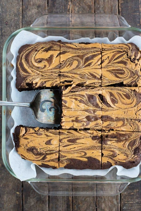 peanut butter swirl brownies cut into squares in glass pan on dark background