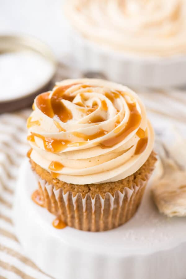 salted caramel frosting piped on cupcake on white background