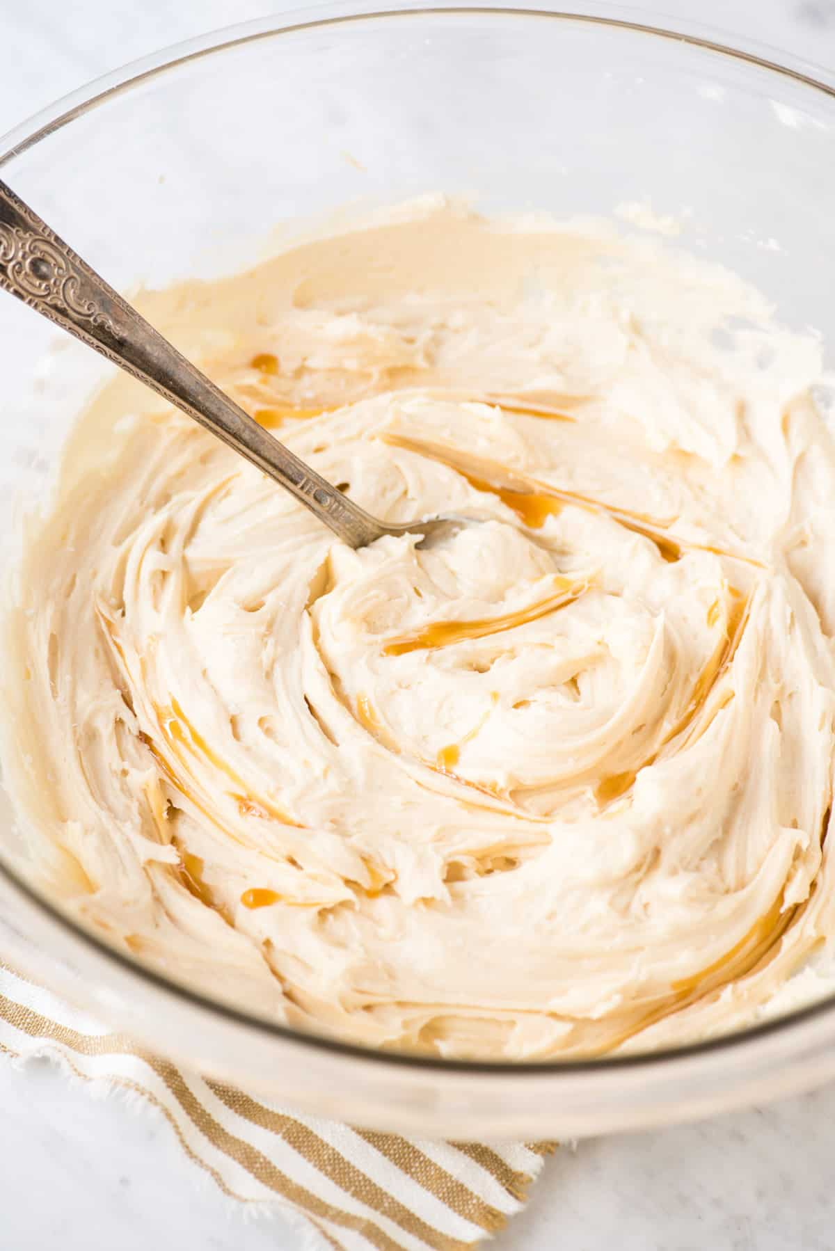 salted caramel frosting with caramel sauce swirled in glass bowl