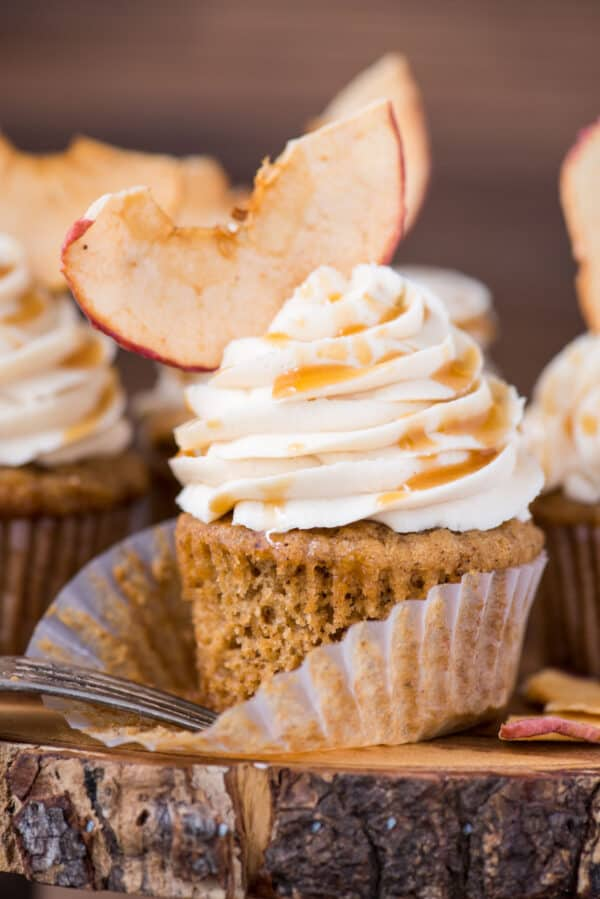 apple spice cupcake with caramel frosting and apple chip on wood cake stand with wood background