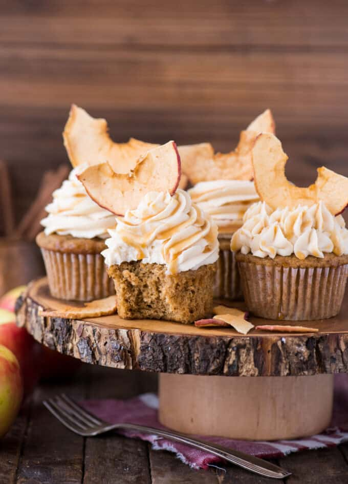 apple spice cupcakes with caramel frosting and apple chips on wood cake stand with wood background