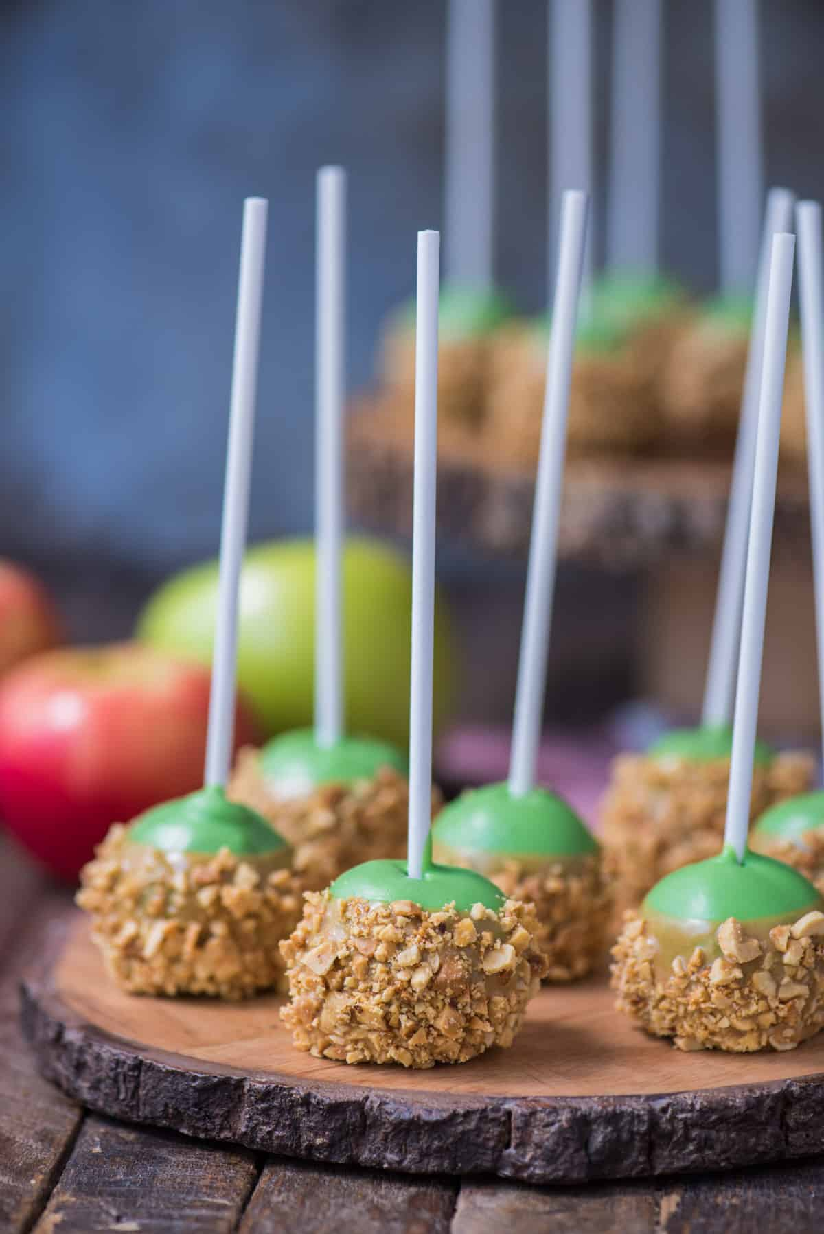 oreo balls that look like caramel apples on round wooden stand with metal background