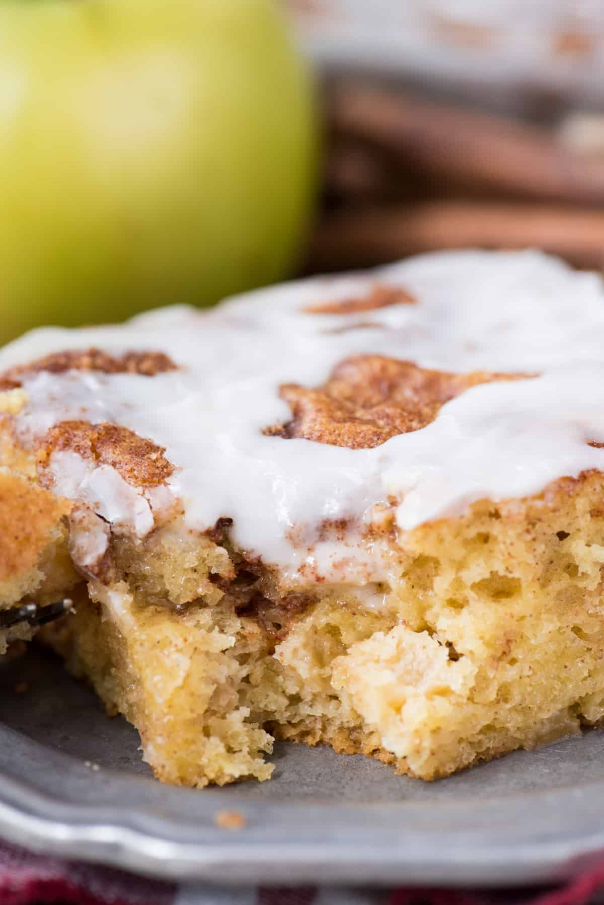 slice of apple coffee cake with white icing on metal place with green apple in background