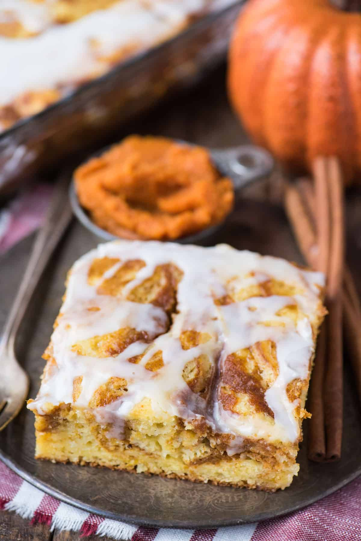 slice of easy pumpkin swirl cake with white icing on metal plate