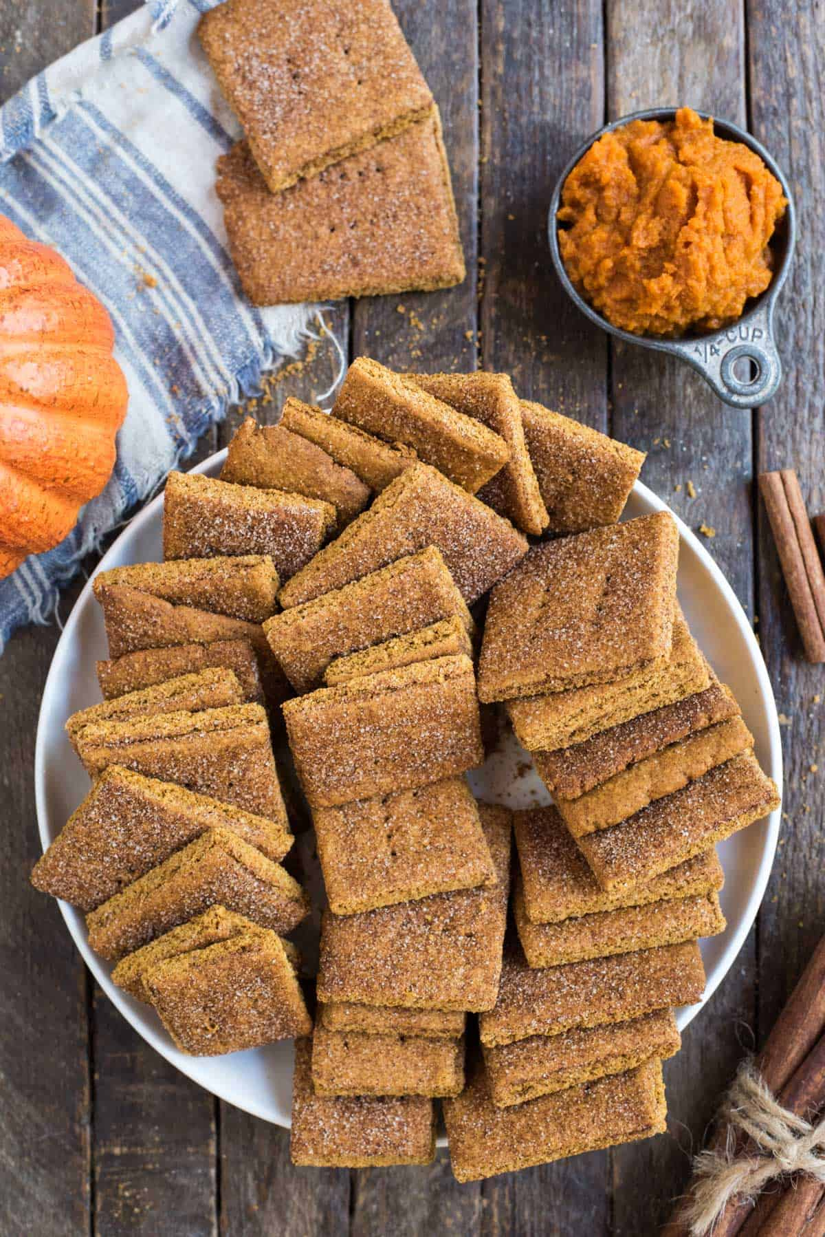 pumpkin graham crackers in a pile in a large white bowl on a wooden background
