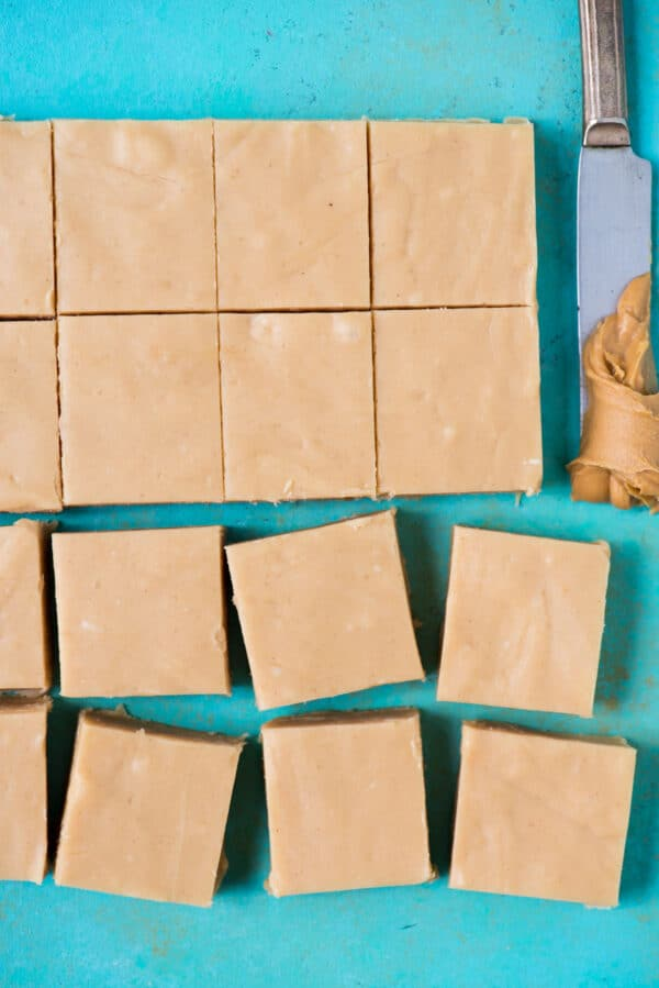 peanut butter fudge cut into pieces on a teal background