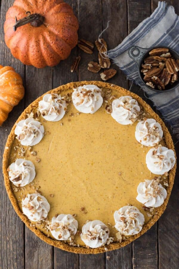 whole pumpkin cheesecake with whipped cream swirls and chopped nuts on wooden background