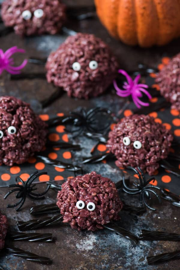 purple spider rice krispie treats with black licorice legs on a dark background
