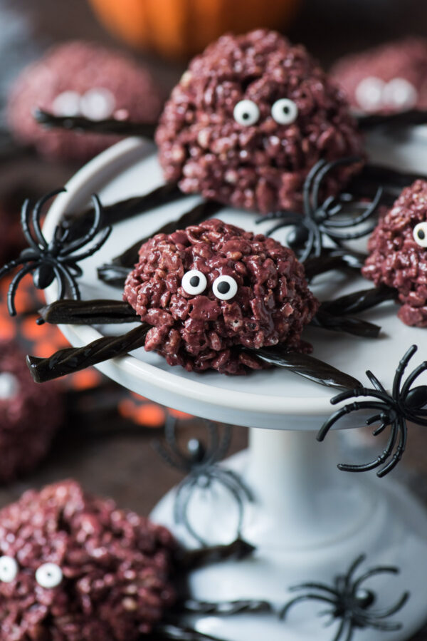 purple spider rice krispie treats with black licorice legs on a gray serving stand