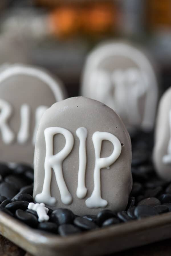 tombstone shape oreo ball in shallow pan surrounded with black rocks