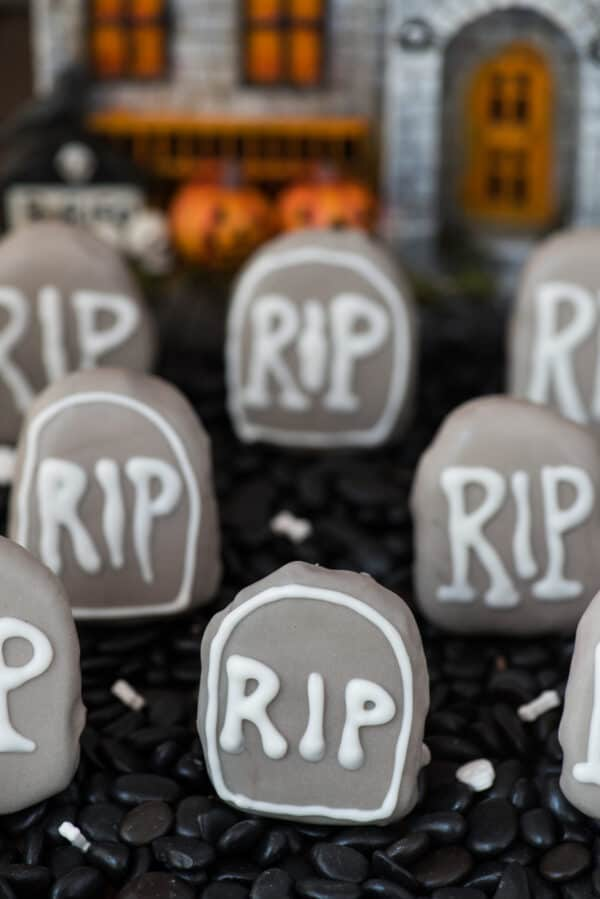 tombstone shape oreo balls in shallow pan surrounded with black rocks with haunted house in the background