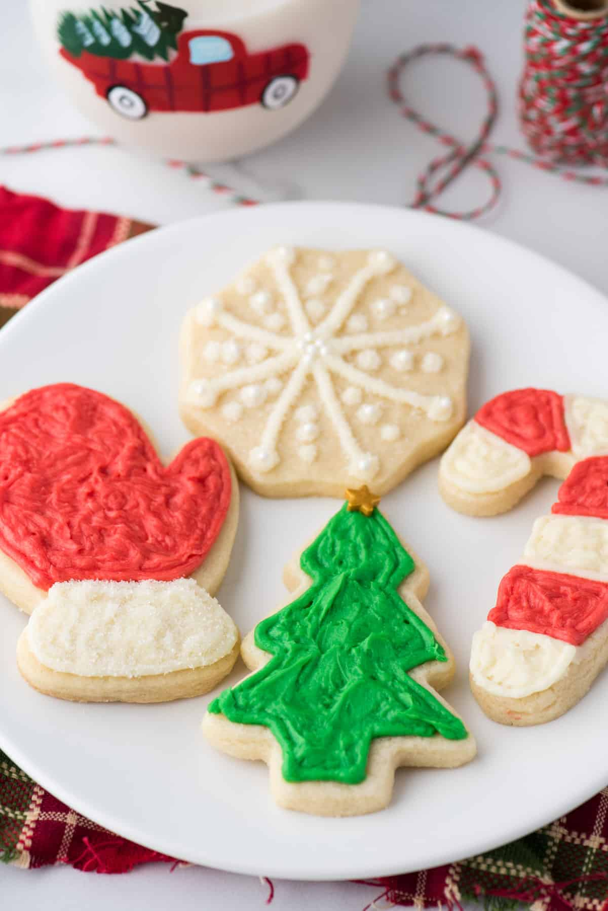 cut out christmas sugar cookies on white plate