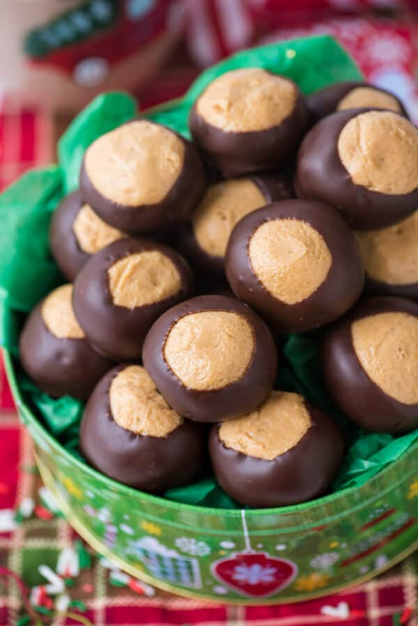peanut butter balls in green christmas cookie tin on red striped towel background