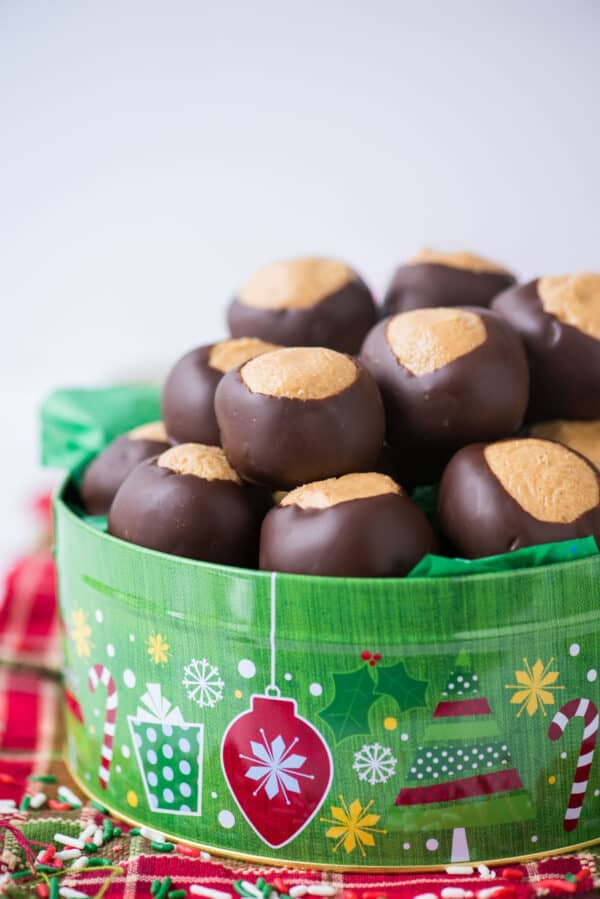 peanut butter balls in green christmas cookie tin with red striped towel under the tin
