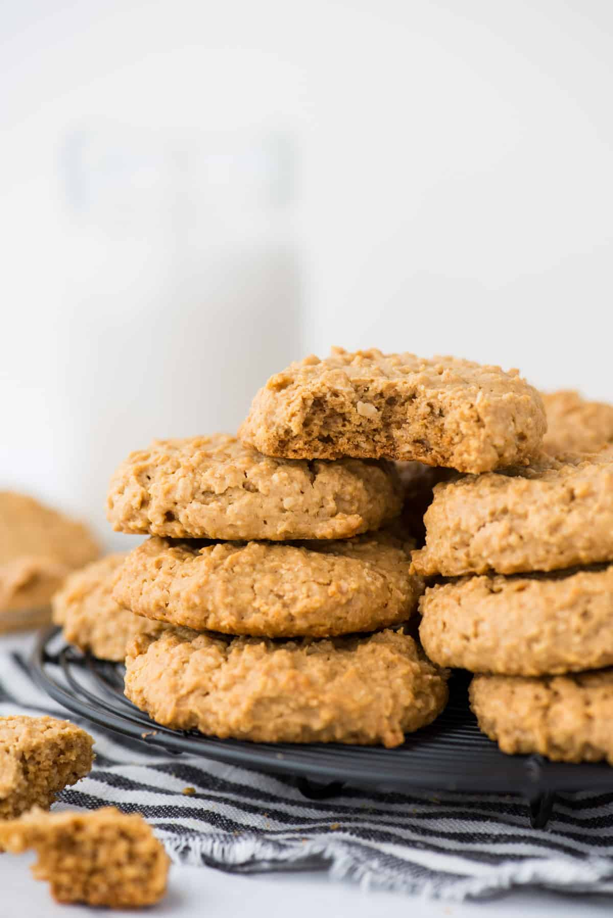 healthy peanut butter cookies in a stack on a black wire cooling rack on white background
