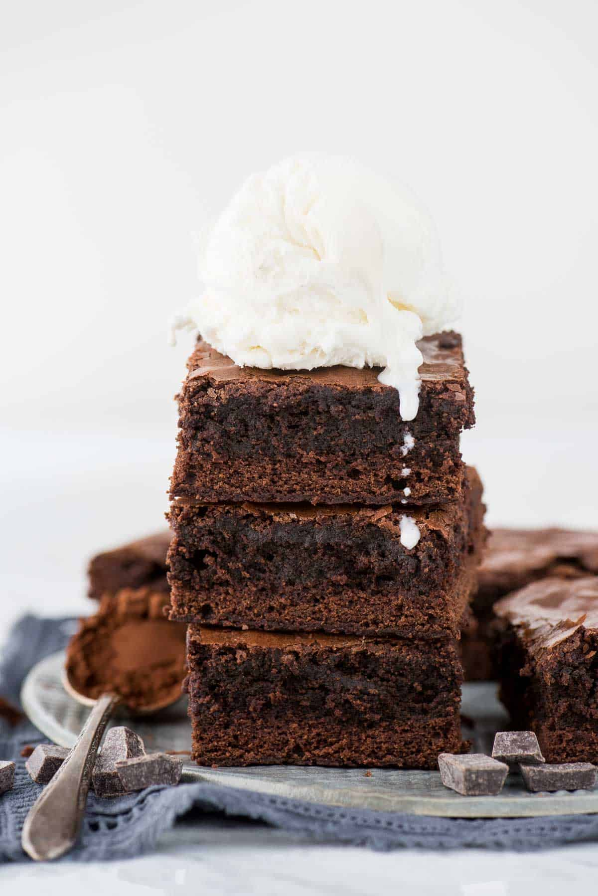 3 brownies in a stack with scoop of vanilla ice cream on top