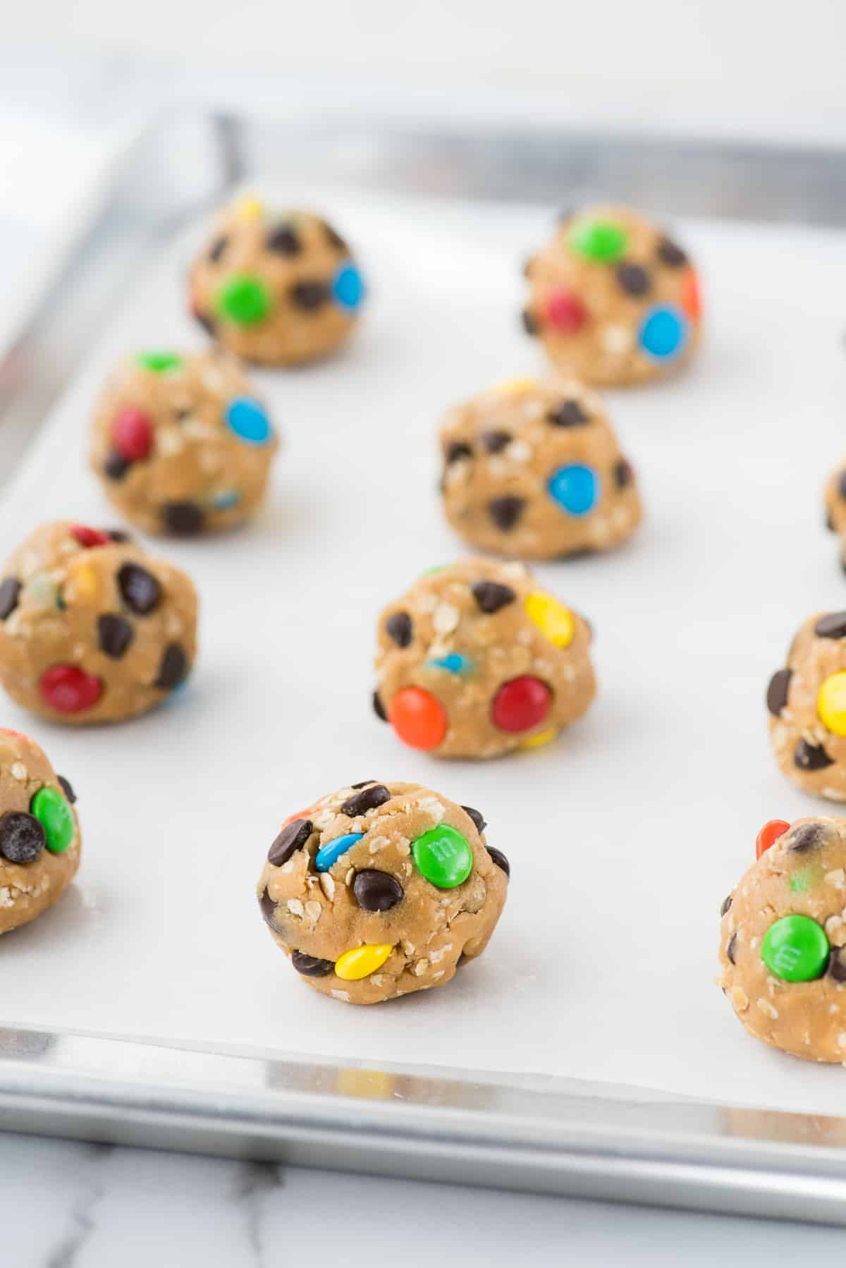 monster cookie dough balls on baking sheet with parchment paper