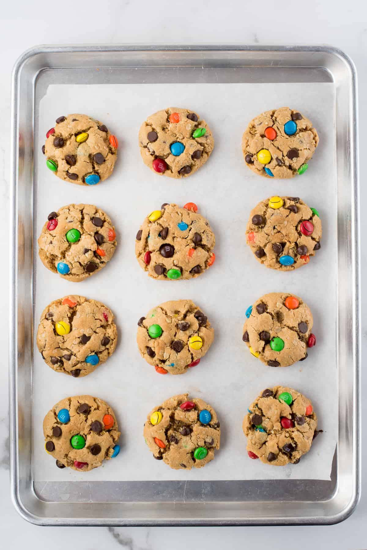 12 monster cookies on baking sheet with parchment paper