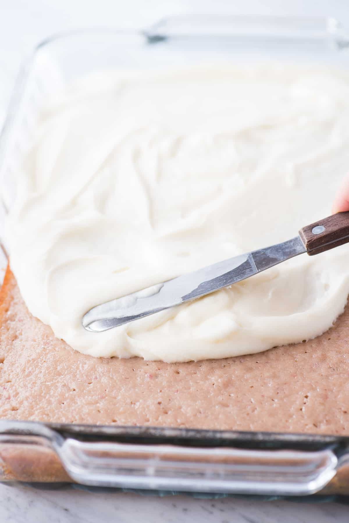 cream cheese frosting being spread onto a cake