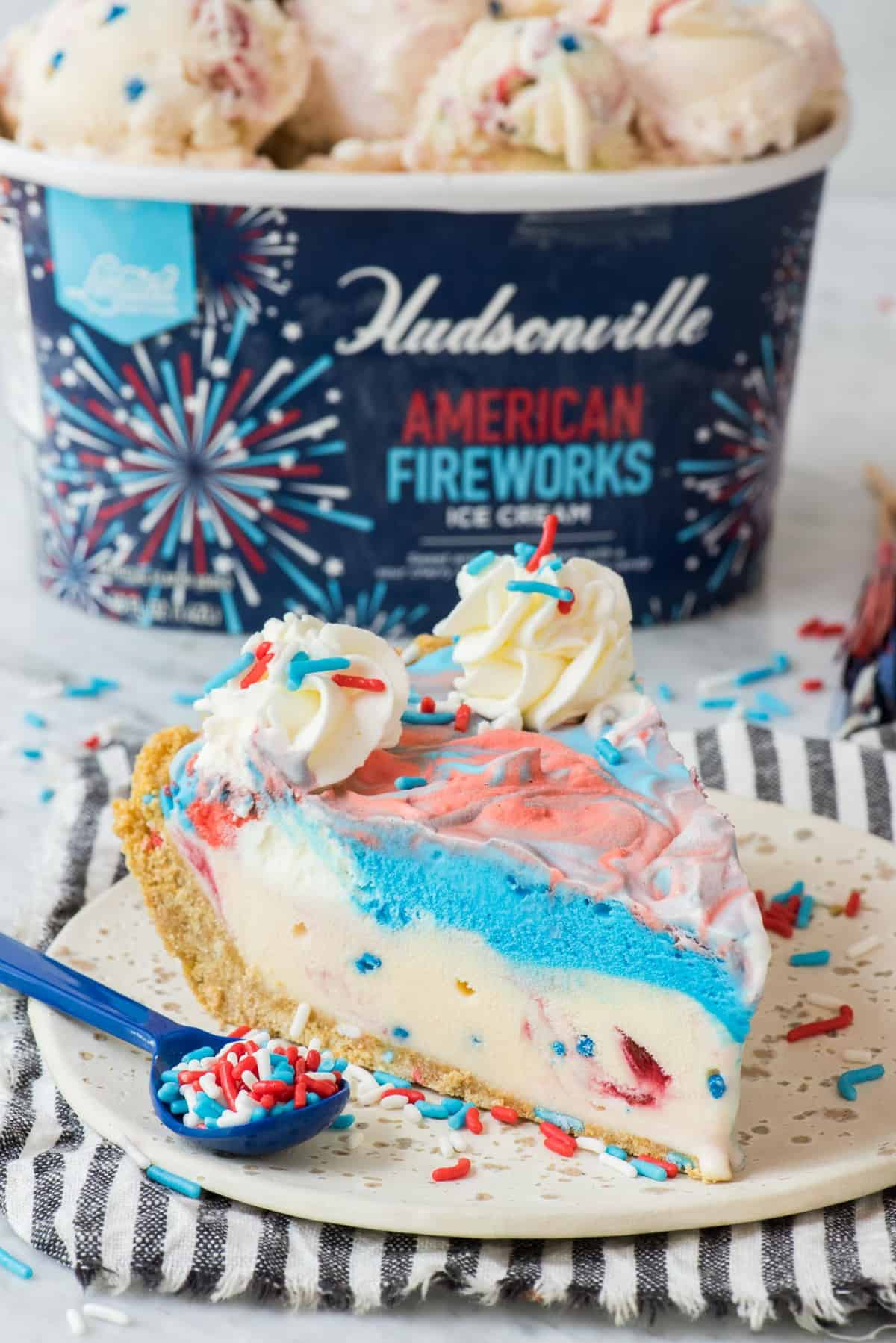 slice of 4th of july red, white and blue ice cream pie on white plate with blue stripe napkin with ice cream container in the background