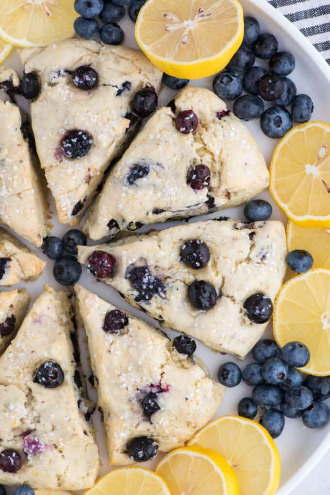 lemon blueberry scones in a circle on white platter surrounded by lemon slices and blueberries