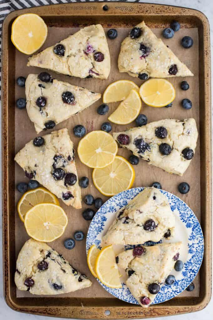 lemon blueberry scones on brown parchment paper with lemon slices and blueberries