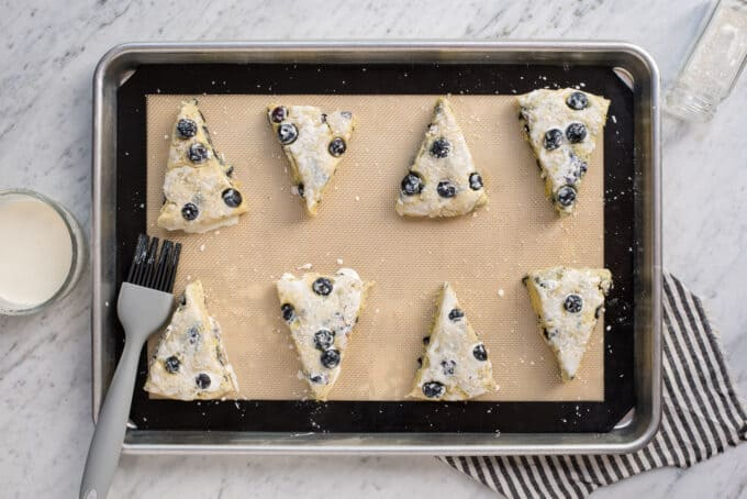 lemon blueberry scones on baking sheet with heavy cream on top