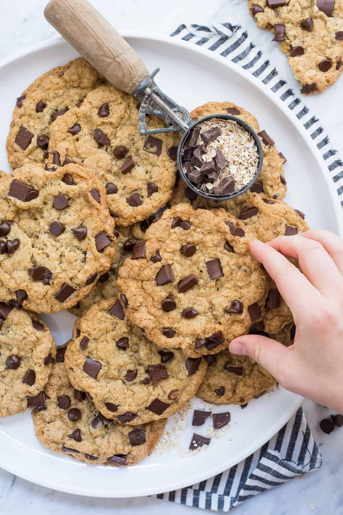 oatmeal chocolate chip cookies on round white tray with hand reaching for cookie