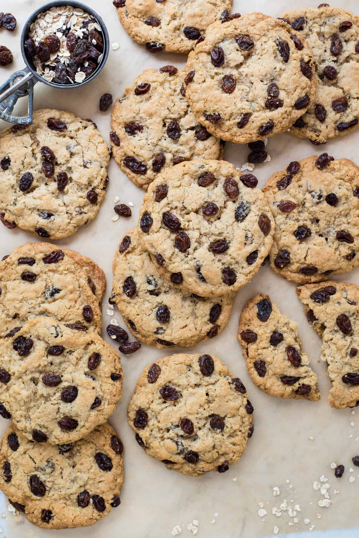 oatmeal raisin cookies on brown parchment paper with raisins and oatmeal spread around