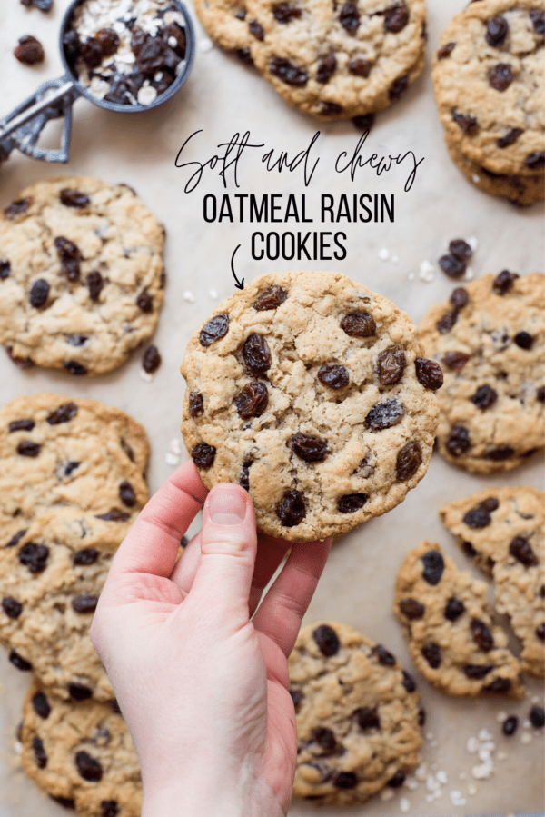 oatmeal raisin cookies on brown parchment paper with raisins and oatmeal spread around with text overlay