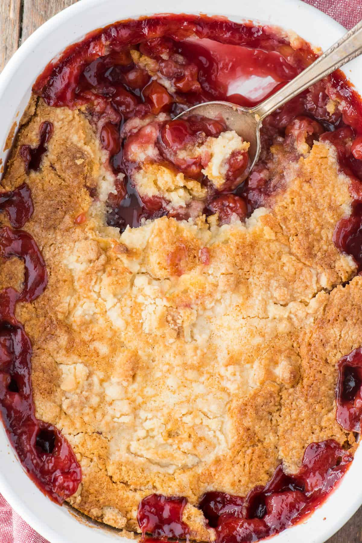 cherry dump cake in white pan on wood background