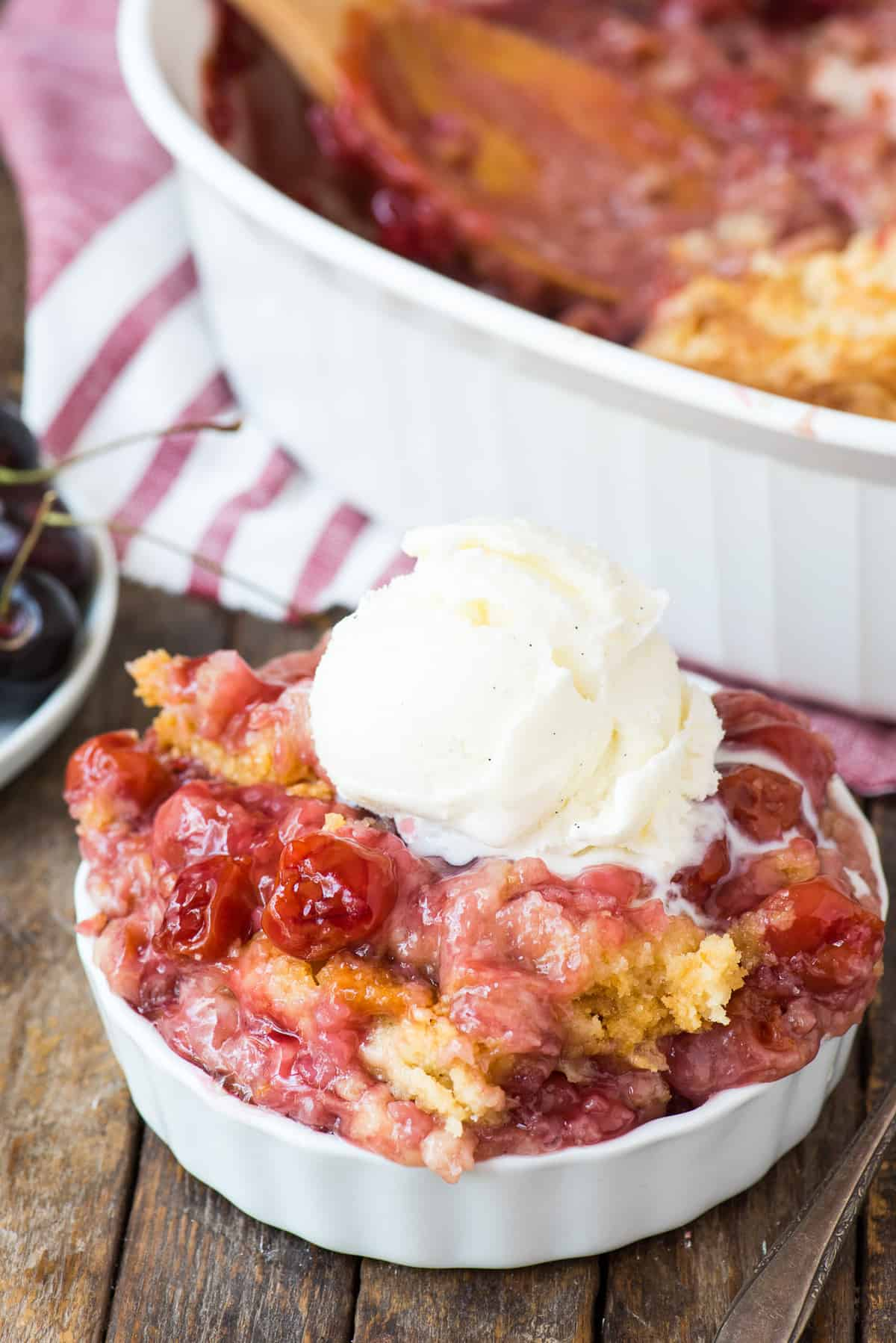 cherry dump cake in white bowl with scoop of vanilla ice cream on top on wood background