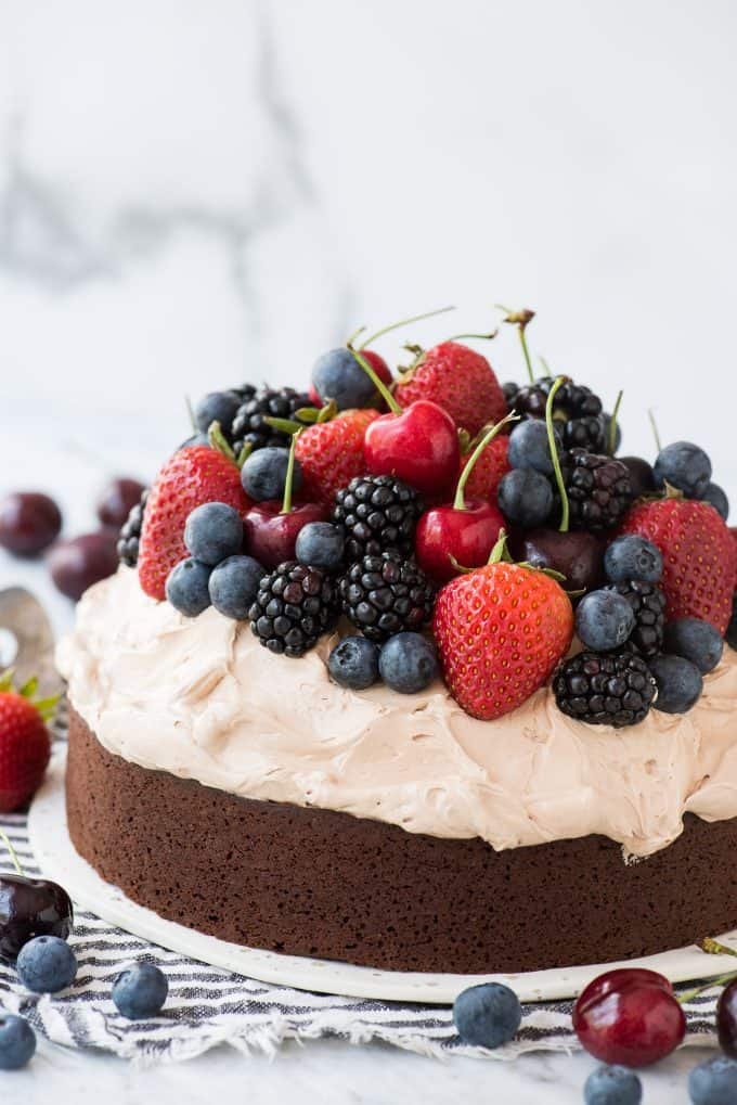 chocolate cake with whipped frosting topped with fresh cherries, strawberries, and blackberries on white plate on white background