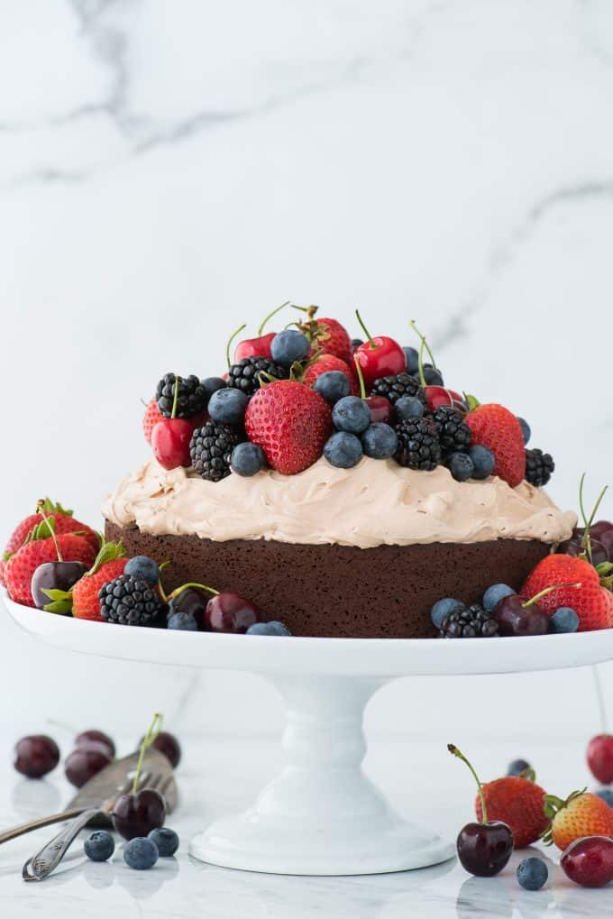 chocolate cake with whipped frosting topped with fresh cherries, strawberries, and blackberries on white cake stand on white background