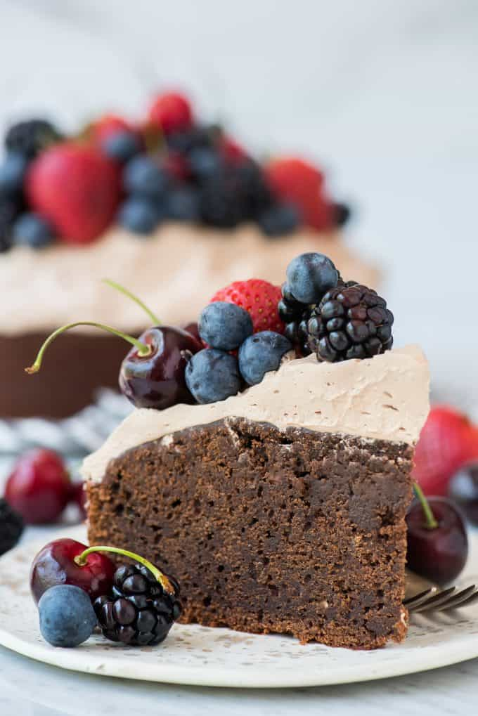 slice of chocolate cake with whipped frosting topped with fresh cherries, strawberries, and blackberries on white plate on white background