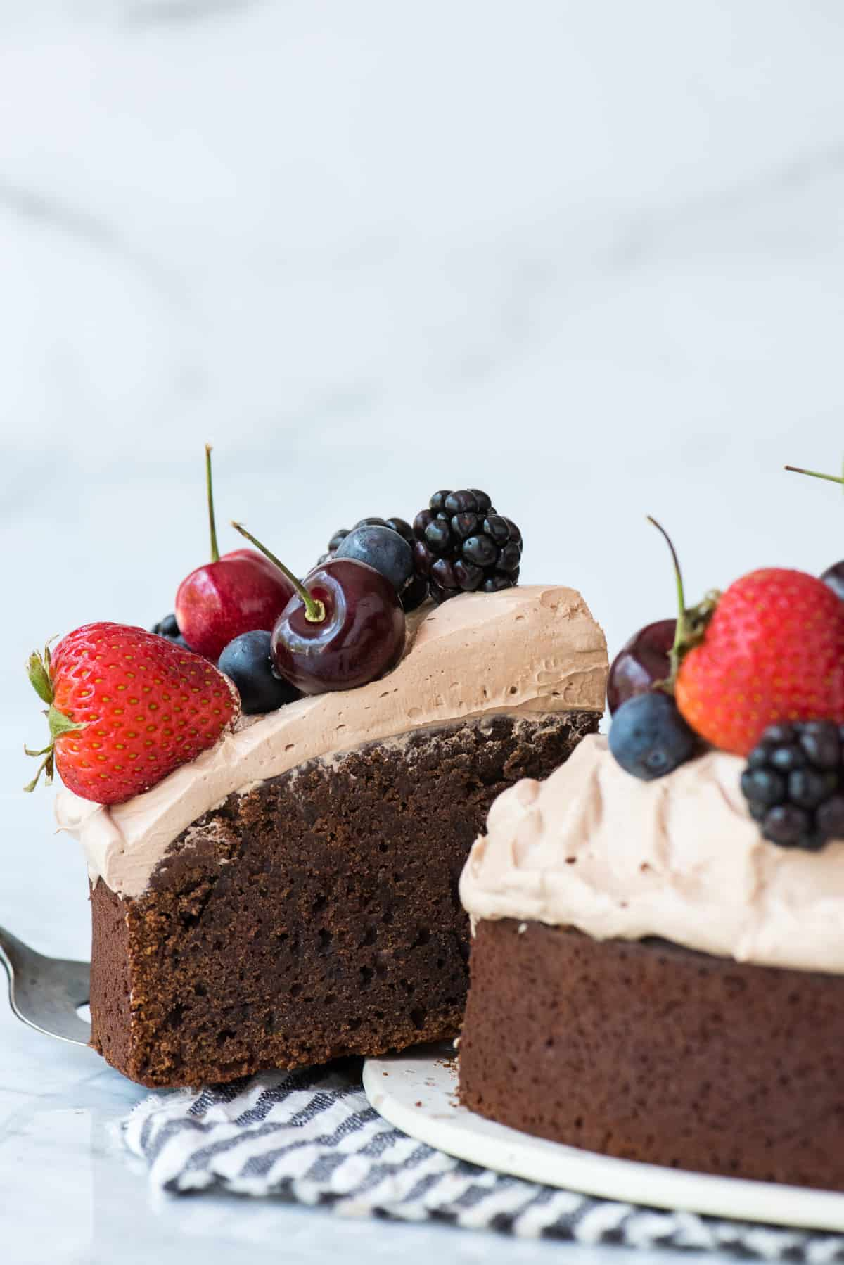 slice of chocolate cake with whipped frosting topped with fresh cherries, strawberries, and blackberries on white plate being removed from cake on white background
