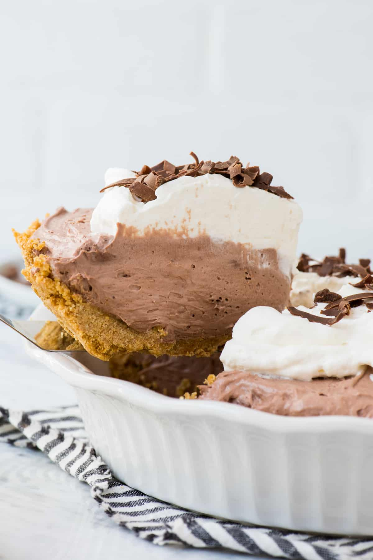 slice of chocolate pudding pie being removed from pie pan
