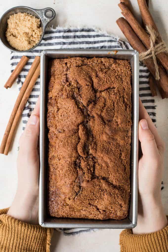 hands holding cinnamon bread in metal loaf pan